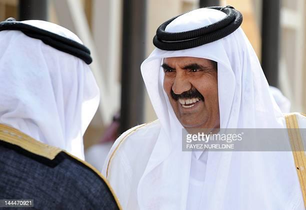 Qatar's Emir Sheikh Hamad bin Khalifa al-Thani talks to an unidentified Saudi official in Riyadh during a welcoming ceremony for leaders attending...