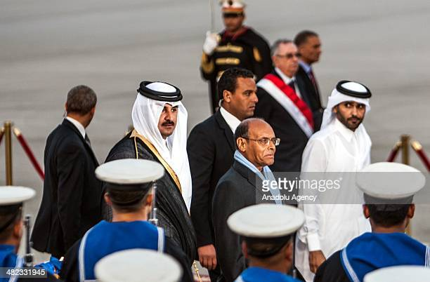 Qatar's Emir Sheikh Tamim bin Hamad Al Thani and Tunisian President Moncef Marzouki walk past an honor guard during an official welcoming ceremony at...