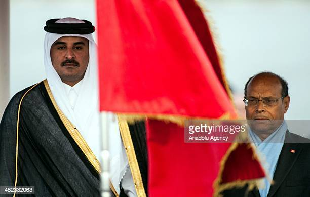 Qatar's Emir Sheikh Tamim bin Hamad Al Thani is welcomed by Tunisian President Moncef Marzouki at Carthage International Airport upon his arrival in...