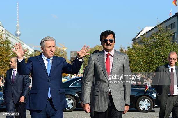 Qatar's Emir Sheikh Tamim bin Hamad Al Thani listens to Berlin mayor Klaus Wowereit as they arrive at the Brandenburg Gate during their meeting in...