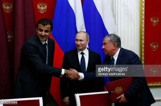 Qatar's Emir Sheikh Tamim bin Hamad alThani Russian President Vladimir Putin and Rosneft chief executive Igor Sechin attend a signing ceremony...
