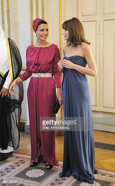 Qatar's First Lady Sheikha Mozah Bint Nasser Al-Misned speaks with French First Lady Carla Bruni-Sarkozy before a diner at the Elysee Palace on June...