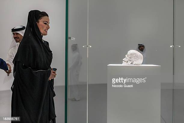 Qatar's First Lady Sheikha Mozah bint Nasser alMissned observing 'For the love of God' a skull made of diamonds at the Relics Exhibition by Damien...