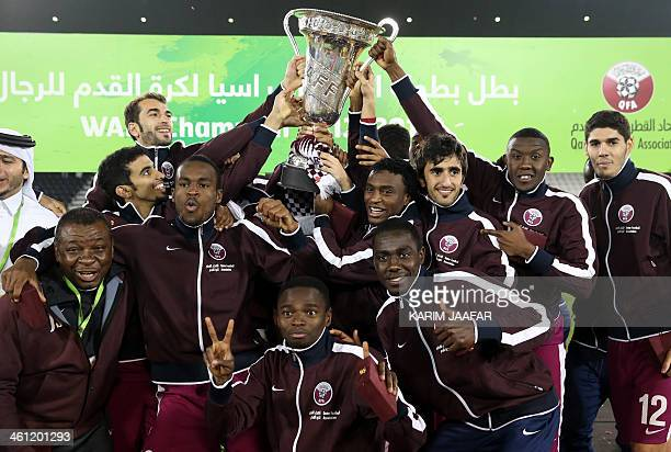 Qatar's football team's players celebrate on the podium with the trophy after winning their final match of the West Asia Football Federation...