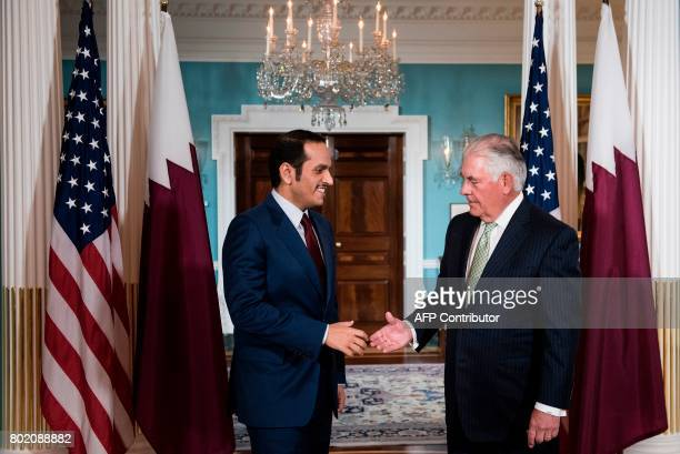 Qatar's Foreign Minister Mohammed bin Abdulrahman alThani and US Secretary of State Rex Tillerson shake hands before a meeting at the US State...