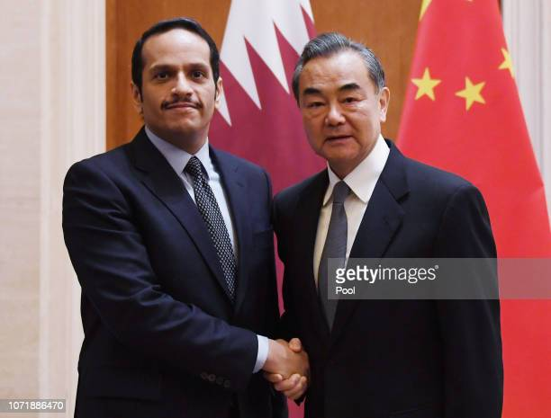 Qatar's Foreign Minister Mohammed bin Abdulrahman bin Jassim Al Thani is greeted by Chinese Foreign Minister Wang Yi before a meeting in Beijing's...