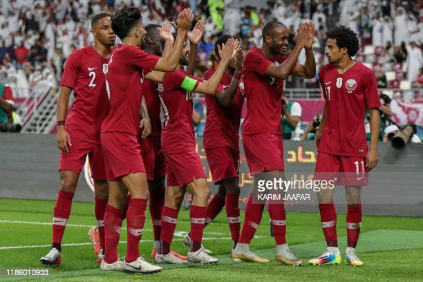 Qatar's forward Akram Afif celebrates with his team after scoring during the 24th Arabian Gulf Cup Group A football match between Qatar and the...