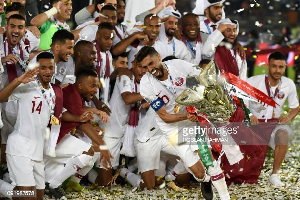 Qatar's forward Hasan Al Haydos raises the cup as the players celebrate their win during the 2019 AFC Asian Cup final football match between Japan...