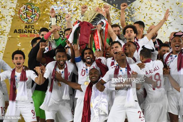 Qatar's forward Hasan Al Haydos raises the cup as the players celebrate their win during the AFC Asian Cup final match between Japan and Qatar at...