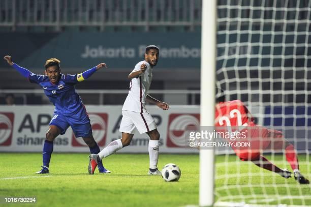 Qatar's goalkeeper Mohammed Al Bakri of Qatar makes a save as Thailand's Chenrop Samphaodi reacts during the men's football Group B match between...