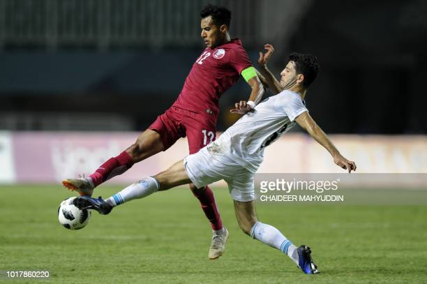 Qatar's Jassem Omer fights for the ball with Uzbekistan's Jaloliddin Masharipov during the men's football preliminary Group B match between Qatar and...
