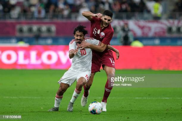 Qatar's Karim Boudiaf and Khalfan Mubarak of the UAE battle for the ball during the Gulf Cup group stage match between Qatar and United Arab Emirates...