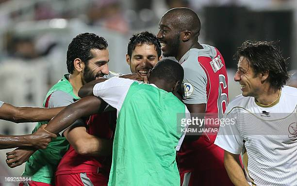 Qatar's Lekhwiya's Mohammed Musa is congratulated by teammates after scoring a second goal against Saudi Arabia's alHilal's during their AFC...