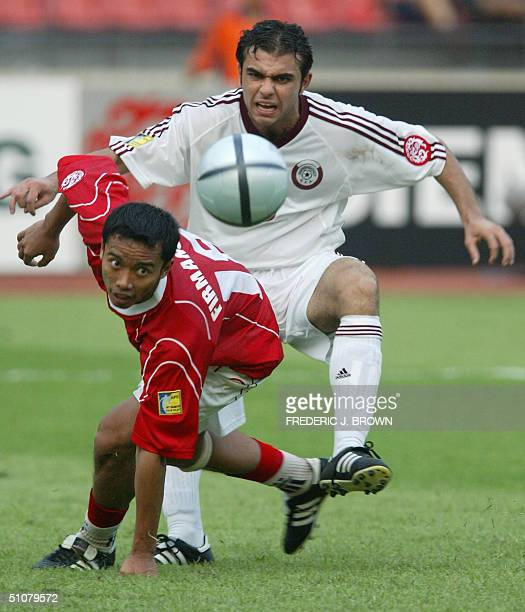 Qatar's Mohammed Gholam and Indonesia's Bambang Pamungkas vie for the ball during a goalmouth scramble in the Asian Cup Group A match at the Workers...