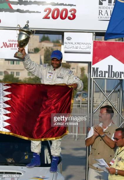 Qatar's Nasser alAttiyah celebrates victory at the Jordan International Rally 26 July 2003 while Prince Faisal bin alHussain brother of King Abdullah...