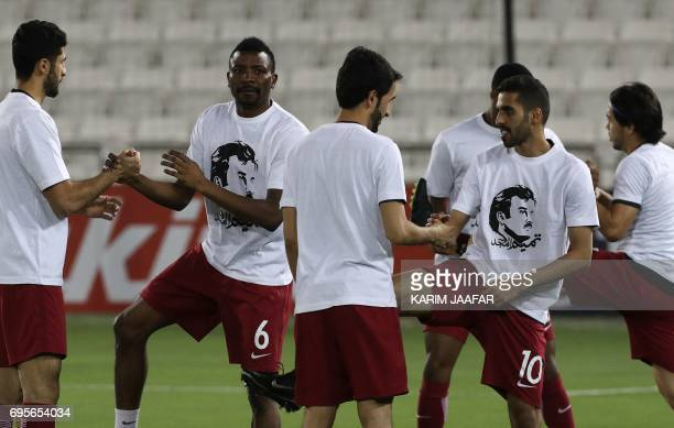 Qatar's national team players wear tshirts bearing portraits of Emir Sheikh Tamim bin Hamad AlThani in support the Qatari leader in the ongoing...