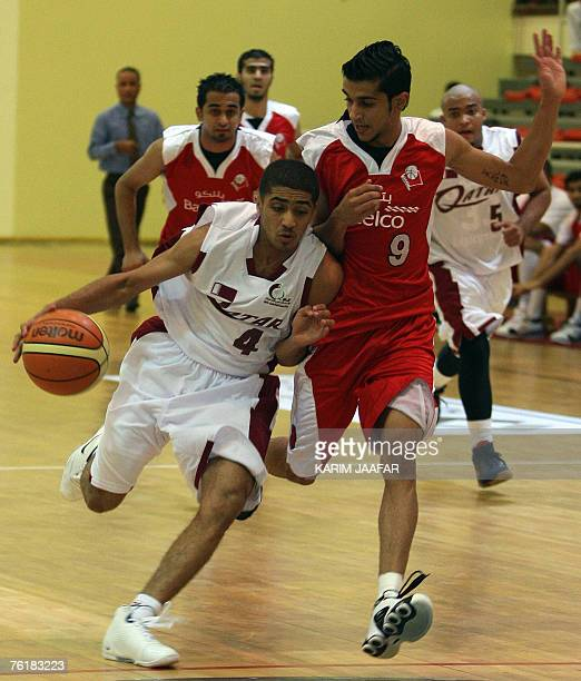 Qatar's player Mansur Atif vies with Mohammed Abdulhakim of Bahrain during their basketball match for the 11th GCC youth basketball championship in...