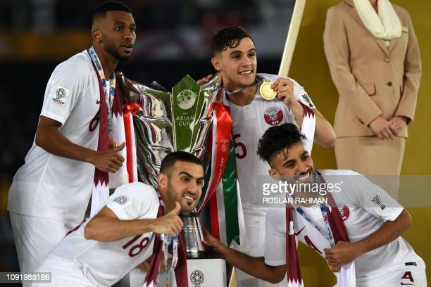 Qatar's players pose for a picture with the trophy after their victory in the 2019 AFC Asian Cup final football match between Japan and Qatar at the...