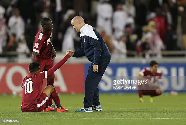Qatar's Spanish coach Felix Sanchez Bas and forward Almoez Ali help up their teammate Akram Hassan Afif as he reacts after losing their AFC U23...