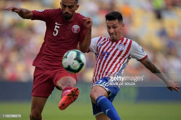 Qatar's Tareq Salman and Paraguay's Hernan Perez vie for the ball during their Copa America football tournament group match at Maracana Stadium in...