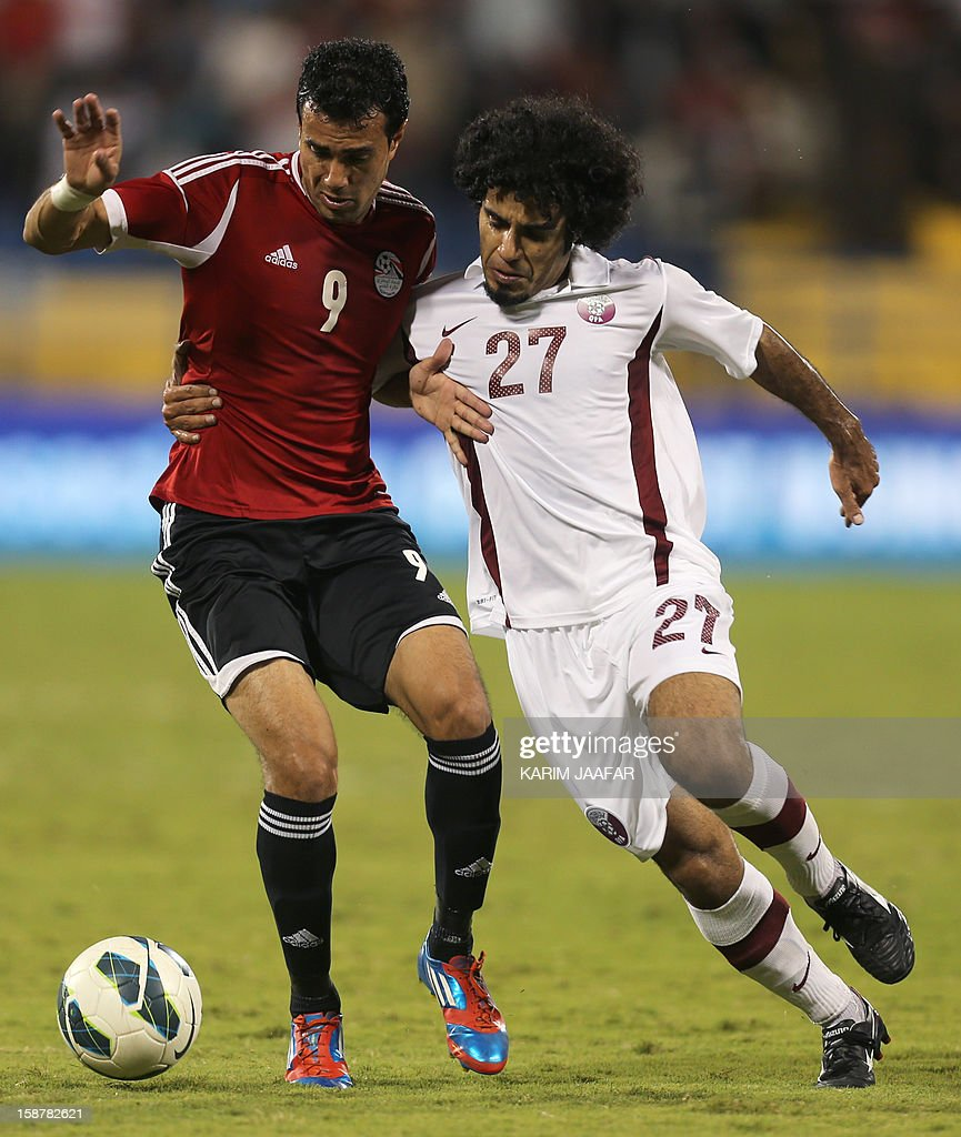 Qatar's Yunes Ali (R) challenges Egypt's Ahmed Mekki during their friendly football match in the Qatari capital Doha on December 28, 2012.