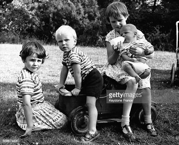 Qautre jeunes enfants dans un jardin dont une petite fille qui donne le biberon à un bébé le 27 juillet 1961 à Londres RoyaumeUni