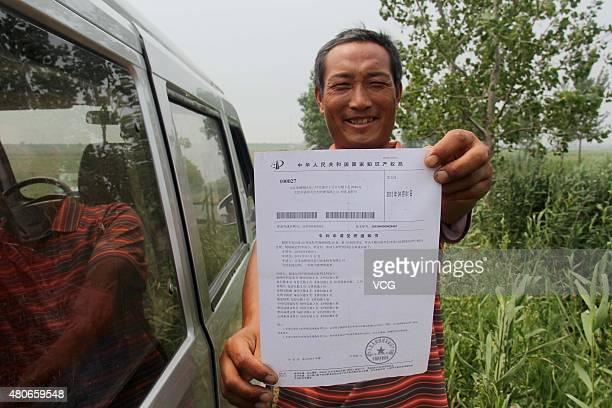Qi Mingjun shows patent notice of his homemade helium balloon spraying machines on July 14 2105 in Lianyungang Jiangsu Province of China Worker Qi...