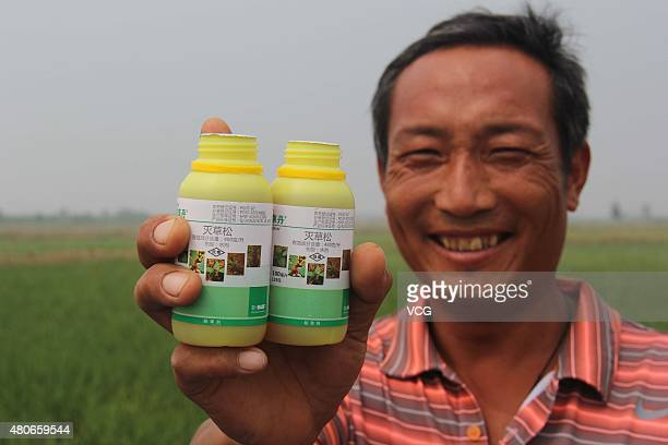 Qi Mingjun shows pesticides used in his homemade helium balloon spraying machines on July 14 2105 in Lianyungang Jiangsu Province of China Worker Qi...