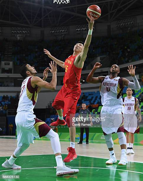 Qi Zhou of China shoots over Anthony Perez of Venezuela in the men's preliminary round group A game 33 against Venezuela on Day 5 of the Rio 2016...