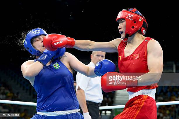 Qian Li of China throws a right to the face of Andreia Bandeira of Brazil during the Women's Middleweight Quarterfinal bout on Day 12 of the Rio 2016...
