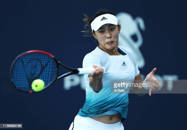 Qiang Wang of China plays a point against Simona Halep of Romania during day 10 of the Miami Open presented by Itau at Hard Rock Stadium on March 27...