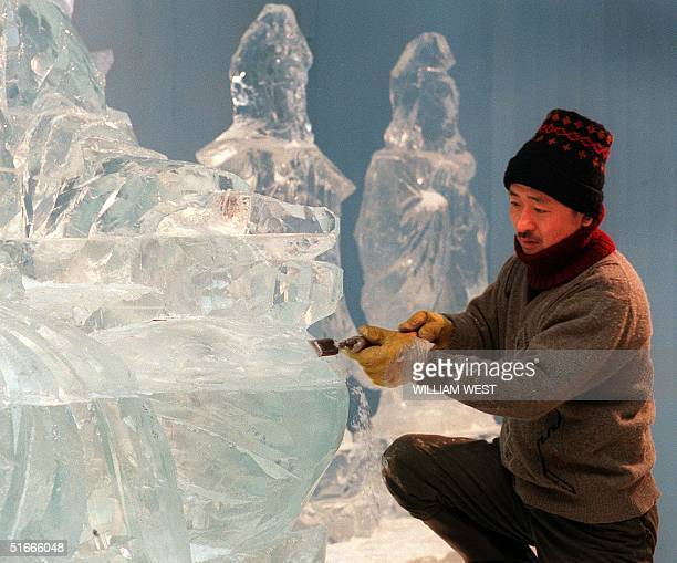 Qiao Chanyi one of twenty master ice carvers from the Chinese province of Harbin puts the final touches to an ice sculpture at the 'Snow and Ice...