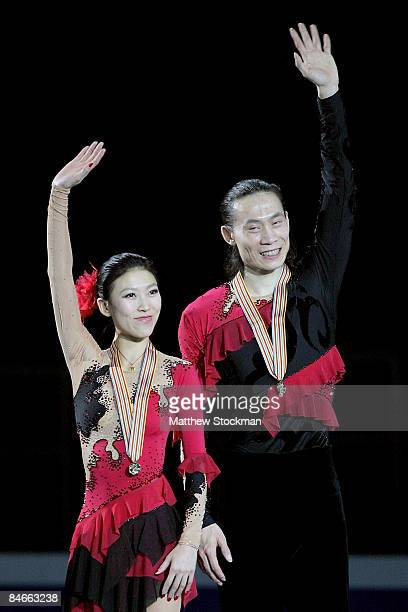 Qing Pang and Jian Tong of China acknowledge the crowd from the winners podium after the Pairs Free Skate during the ISU Four Continents Figure...