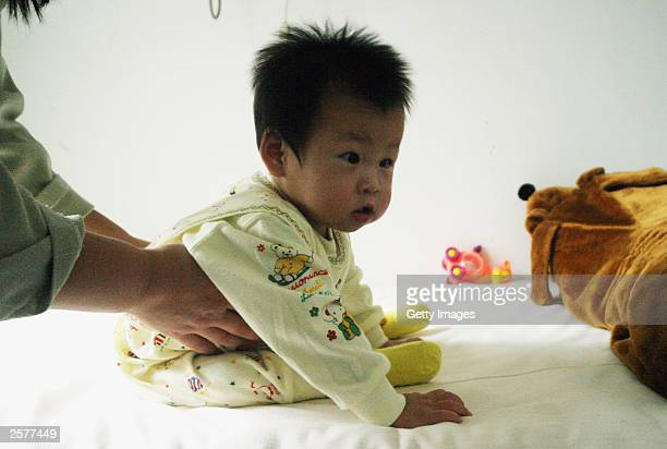 QingQing a 15 month old infant is seen at the Dongzhimen hospital on October 10 2003 in Beijing China QingQing was born with an extra leg that was...
