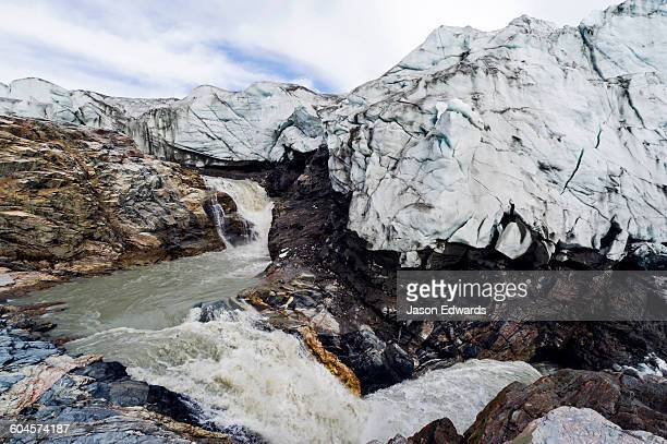 a waterfall of meltwater cascades from beneath a glacier fracture zone. - gneiss stock pictures, royalty-free photos & images