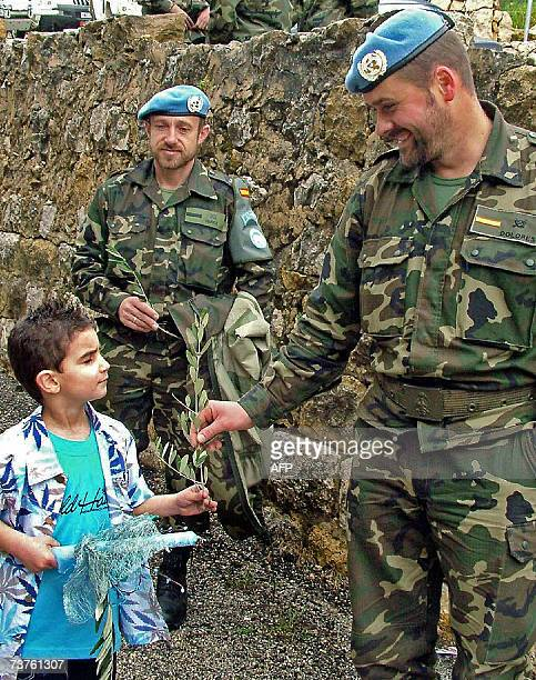 A Lebanese boy hands a Spanish UN soldier an olive branch outside a church in the southern Christian village of Qleyaa 01 April 2007 during the...