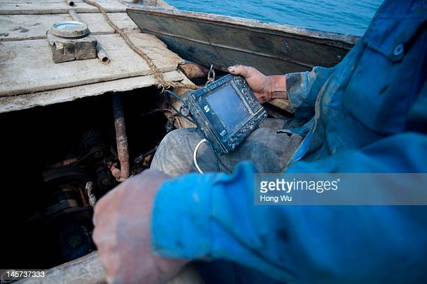 Qu Lin a 45yearold Chinese fisherman uses GPS to fish on his 8 meters long fishing boat lonely as he no money to employ helper on May 28 2012 in...