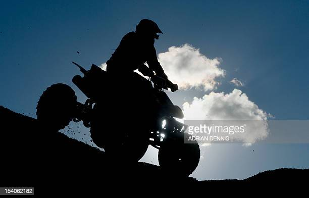 A quad bike rider comes over the crest of a dune during the main quad and sidecar race during the 2012 RHL Weston beach race in WestonSuperMare...