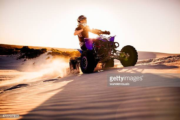 Quad racer driving up a sand dune with sun flare