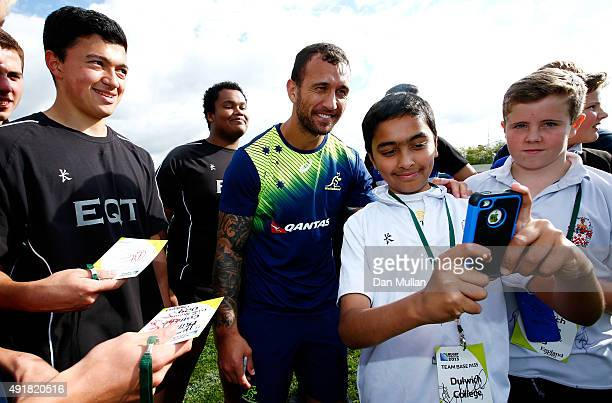 Quade Cooper of Australia poses for a photo with school pupils following a training session at Dulwich College on October 8, 2015 in London, United...