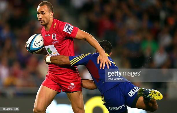 Quade Cooper of the Reds is tackled by Buxton Popoalii of the Highlanders during the round seven Super Rugby match between the Highlanders and the...
