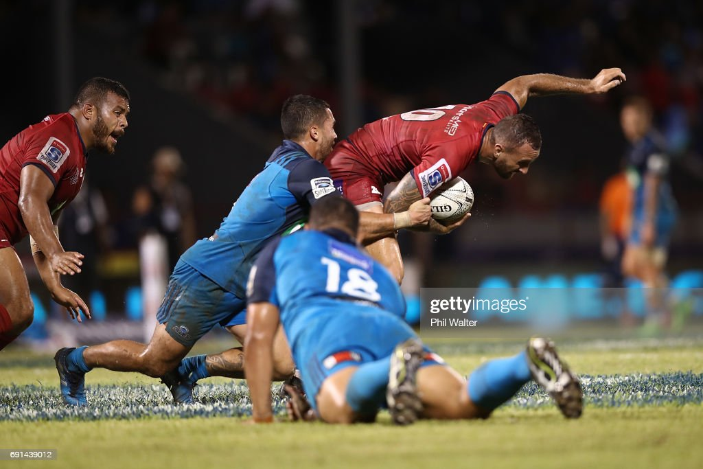 Quade Cooper of the Reds is tackled during the round 15 Super Rugby match between the Blues and the Reds at Apia Park National Stadium on June 2, 2017 in Apia, Samoa.