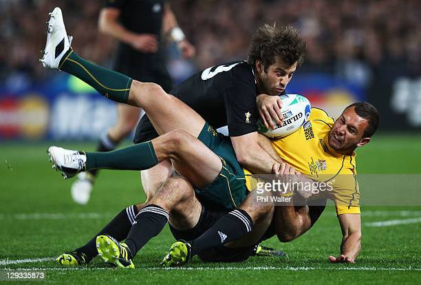 Quade Cooper of the Wallabies is tackled by Conrad Smith of the All Blacks during semi final two of the 2011 IRB Rugby World Cup between New Zealand...