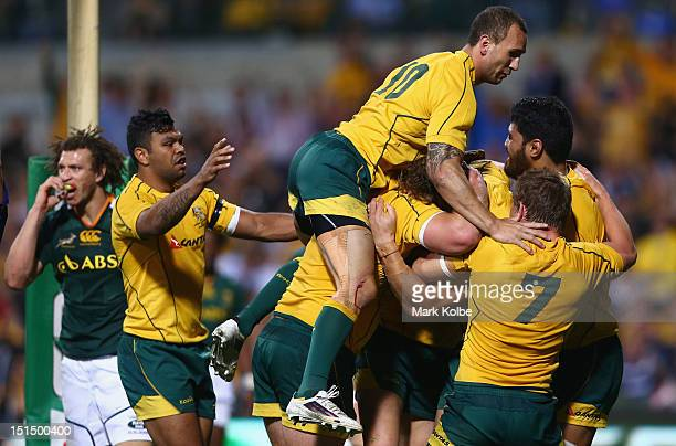 Quade Cooper of the Wallabies jumps on his team mates as they celebrate with Scott Higginbotham of the Wallabies after scoring a try during Rugby...