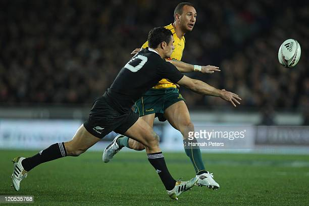Quade Cooper of the Wallabies kicks the ball through past Daniel Carter of the All Blacks during the Tri-Nations Bledisloe Cup match between the New...