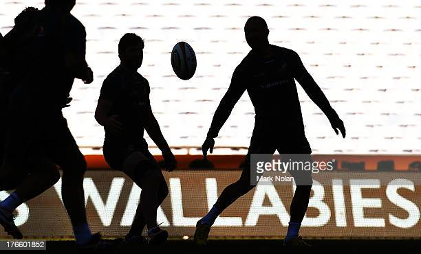 Quade Cooper passes the ball during the Australian Wallabies Captain's Run at ANZ Stadium on August 16 2013 in Sydney Australia