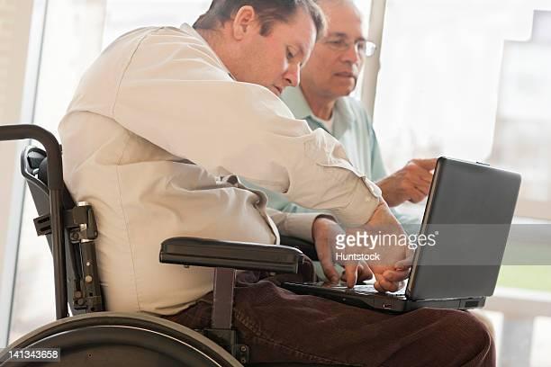 quadriplegic man with spinal cord injury in wheelchair using his thumb to type on computer - quadriplegic fotografías e imágenes de stock