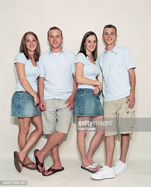 Quadruplet brothers and sisters standing by wall, smiling, portrait