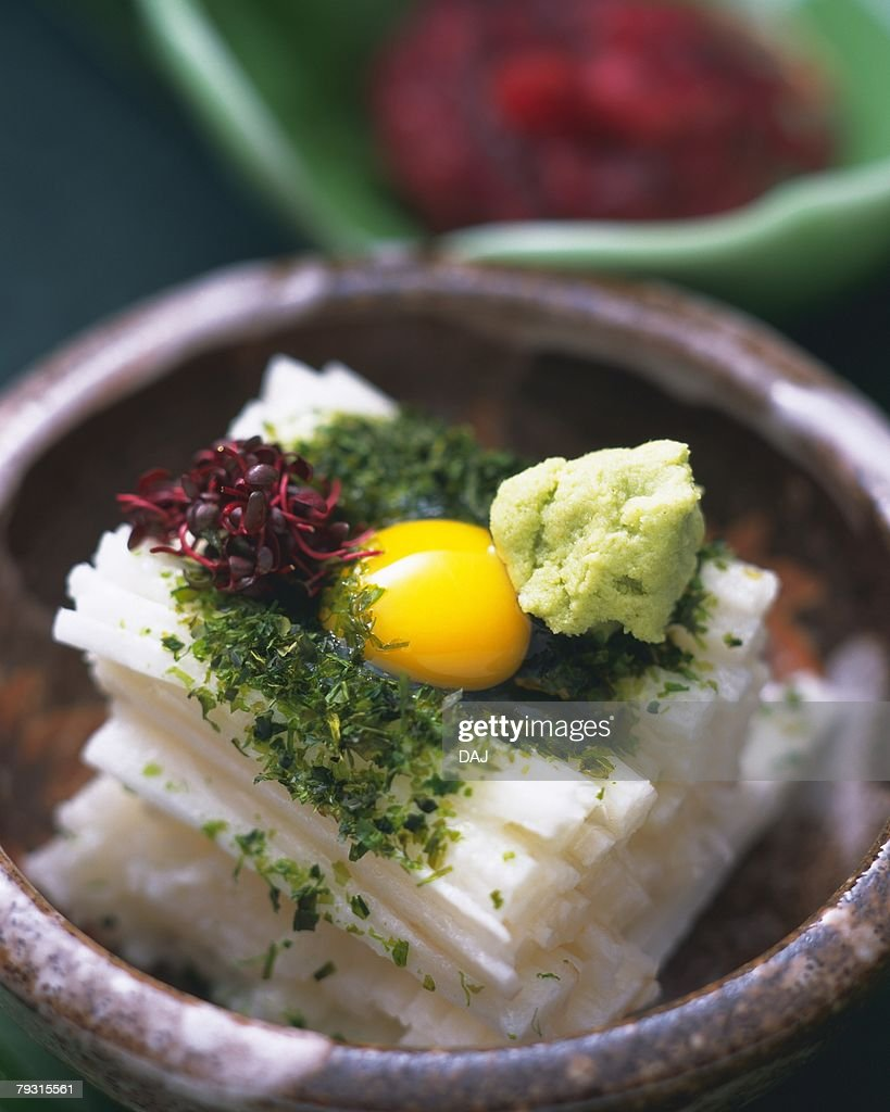 Quail egg on yam cut into strips in bowl, high angle view, differential focus : Foto de stock