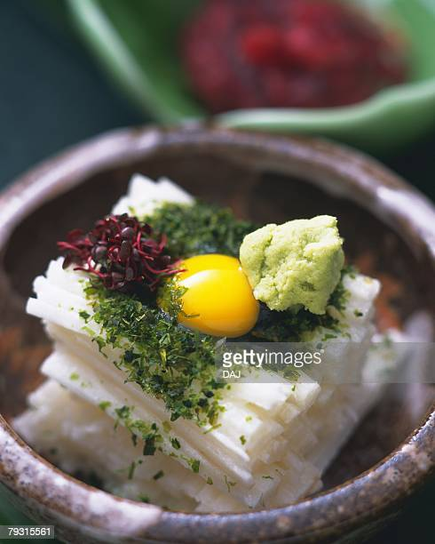 Quail egg on yam cut into strips in bowl, high angle view, differential focus